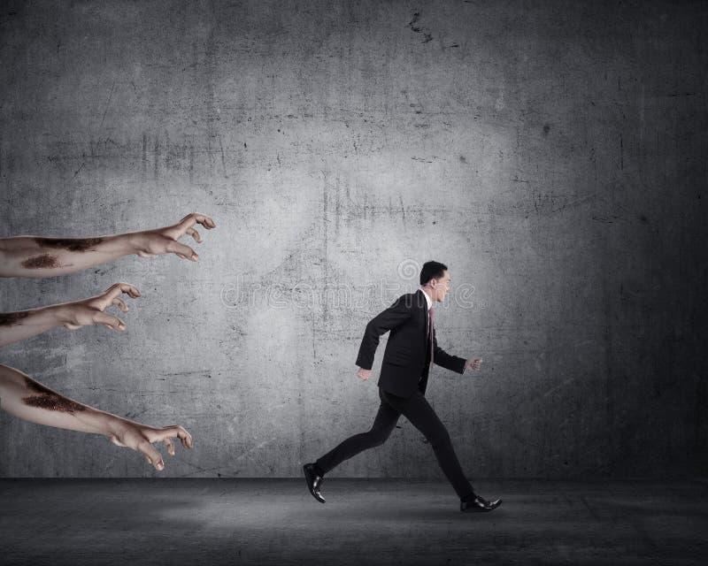 Homem de negócio que corre com zombi fotografia de stock royalty free