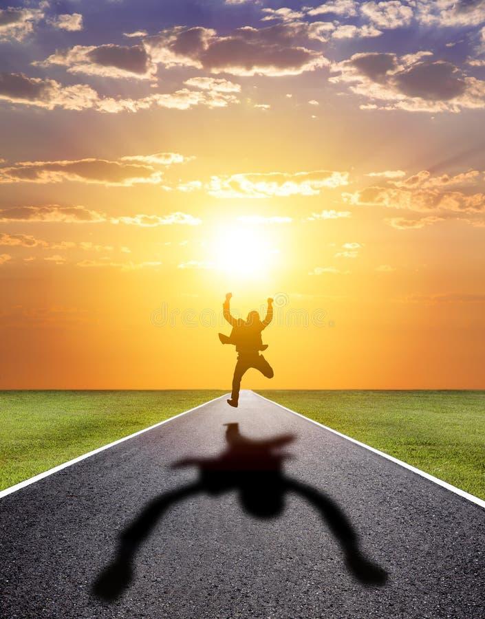 Homem de negócio que corre felizmente à estrada bem sucedida com por do sol imagem de stock royalty free
