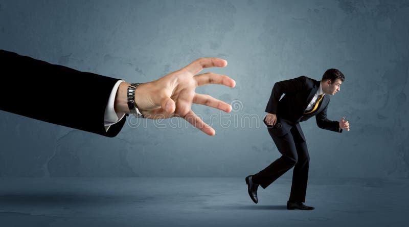 Homem de negócio que corre longe de um conceito enorme da mão fotos de stock royalty free