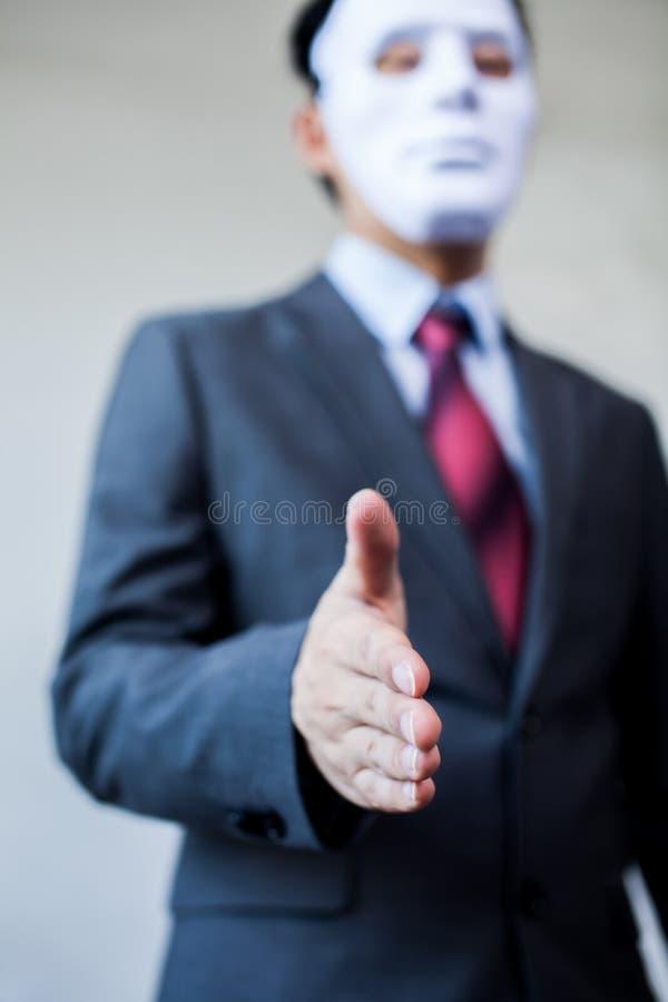 Homem de negócio que dá o aperto de mão desonesto que esconde na máscara - fraude do negócio e acordo da hipócrita imagem de stock
