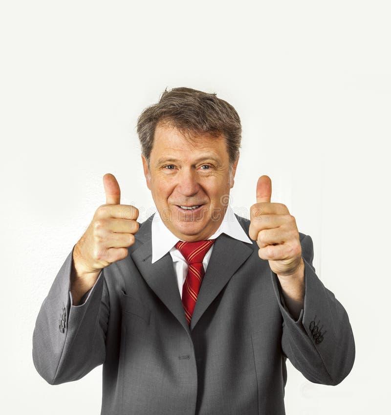Homem de negócio que dá os polegares acima do sinal fotografia de stock