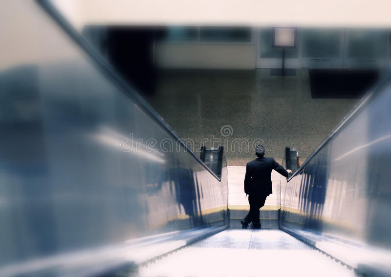 Homem de negócio que desce abaixo da escada rolante imagem de stock