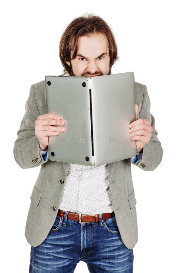Homem de negócio que esconde atrás de seu laptop em suas mãos Emo fotografia de stock royalty free