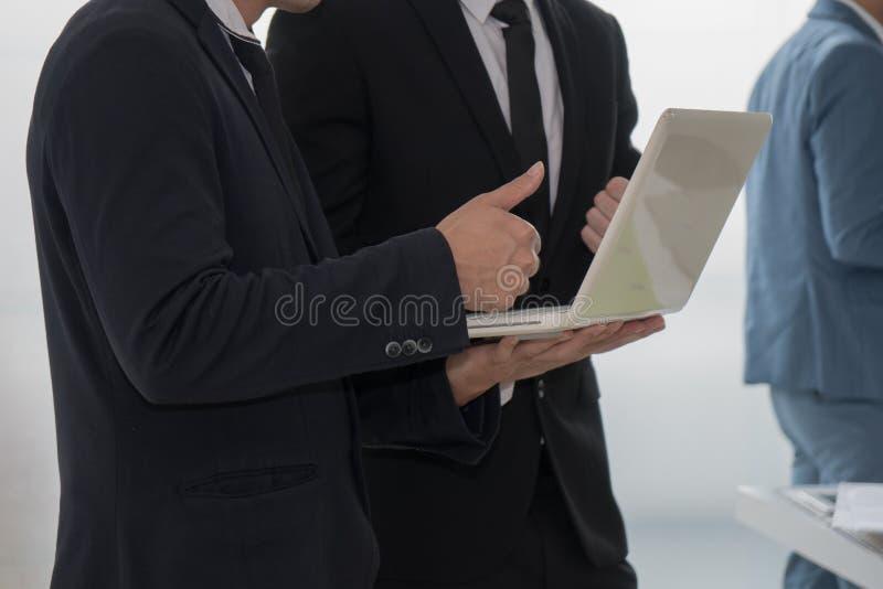 Homem de negócio que está e que mostra trunfos até seu colega à ré imagens de stock royalty free