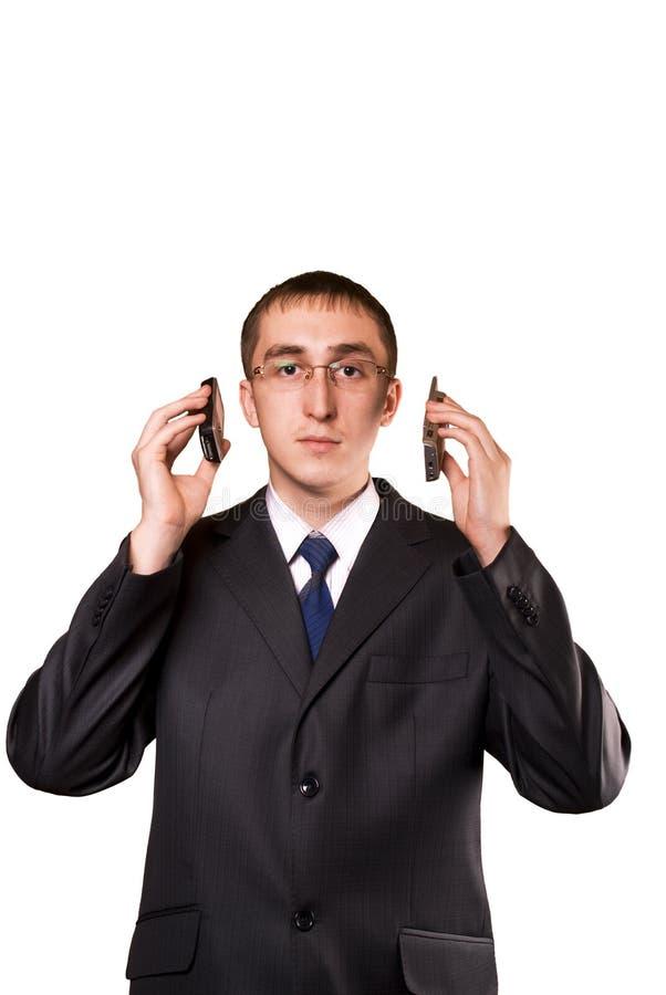 Homem de negócio que fala em um telemóvel dois fotos de stock royalty free