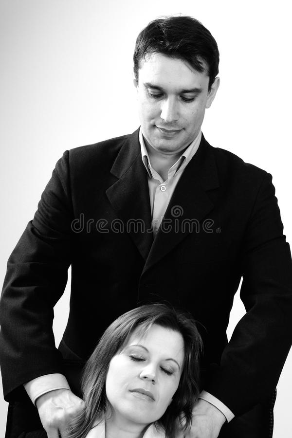 Homem de negócio que faz massagens a mulher fotografia de stock royalty free