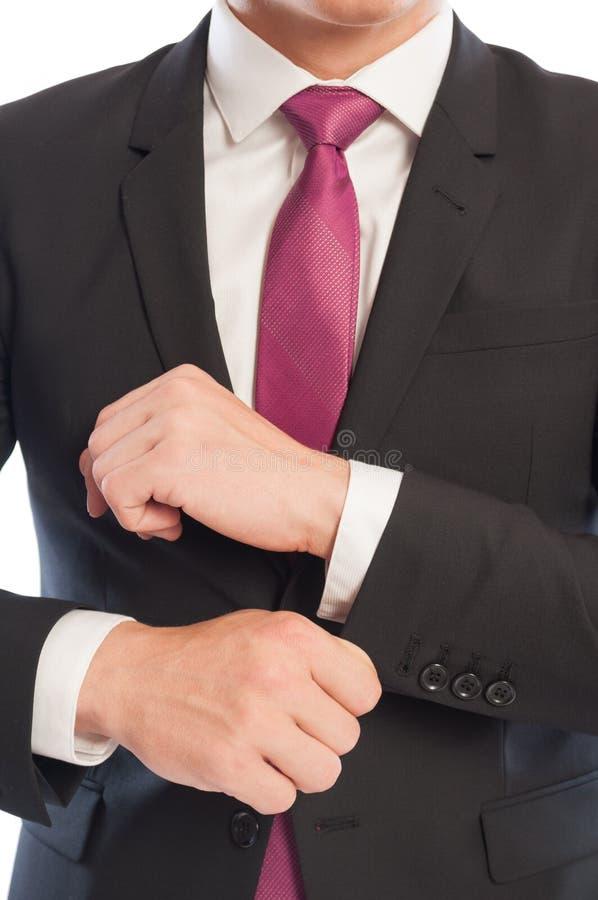 Homem de negócio que fixa sua luva da camisa imagens de stock