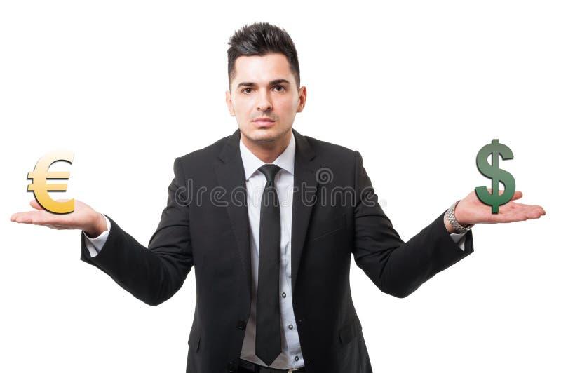 Homem de negócio que guarda o euro e os símbolos ou os sinais do dólar imagens de stock royalty free