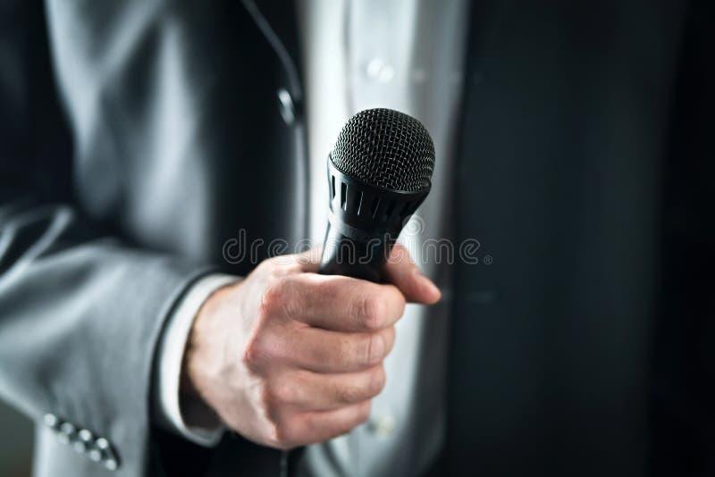 Homem de negócio que guarda o microfone Discurso falador e de doação público no terno para o conceito da audiência imagens de stock royalty free