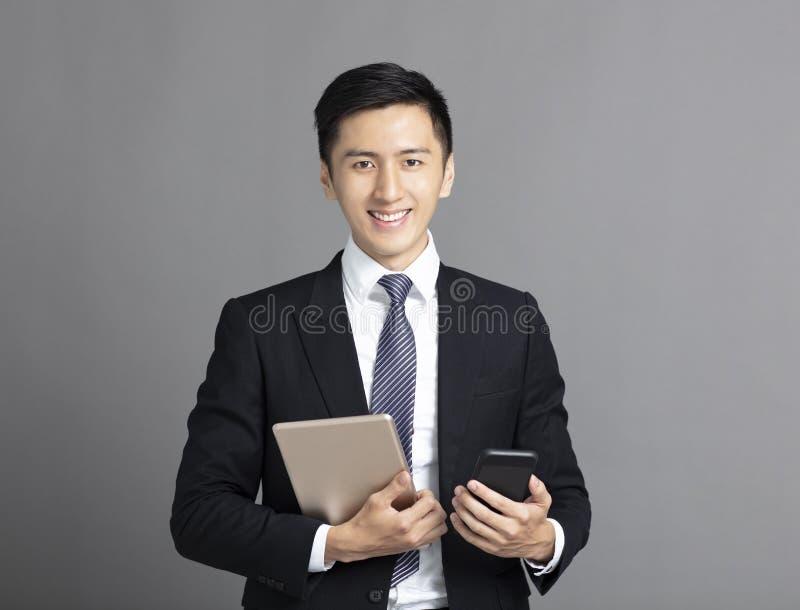 homem de negócio que guarda o PC esperto do telefone e da tabuleta foto de stock royalty free