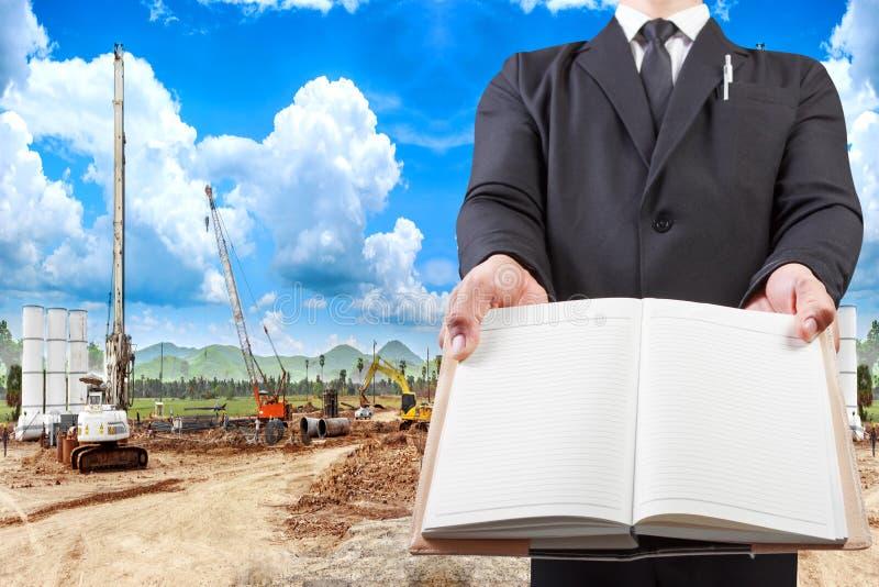 Homem de negócio que guarda a placa do livro local AG da construção civil imagem de stock