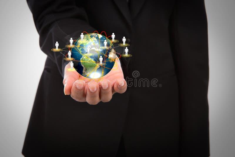 Homem de negócio que guardara o mundo pequeno em suas mãos fotografia de stock royalty free