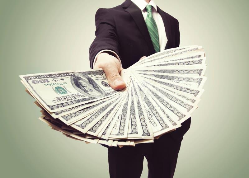 Homem de negócio que indica uma propagação do dinheiro fotografia de stock