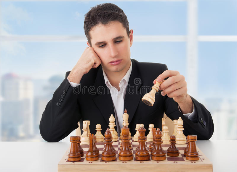 Homem de negócio que joga a xadrez, fazendo o movimento imagem de stock royalty free