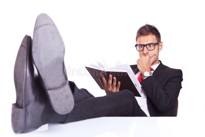 Homem de negócio que lê um livro do filme policial imagens de stock royalty free