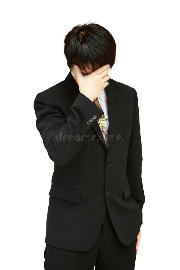 Homem de negócio que mantem sua cabeça na dor de encontro foto de stock