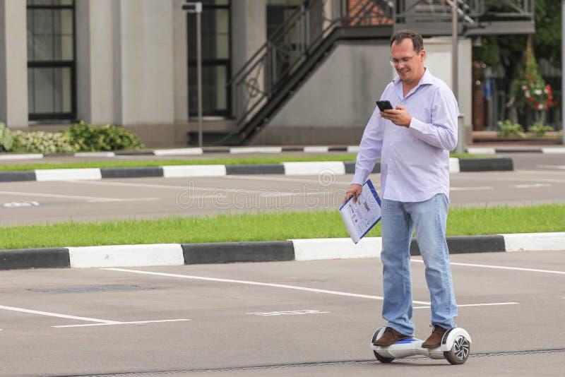 Homem de negócio que monta um 'trotinette' eletrônico fora foto de stock royalty free