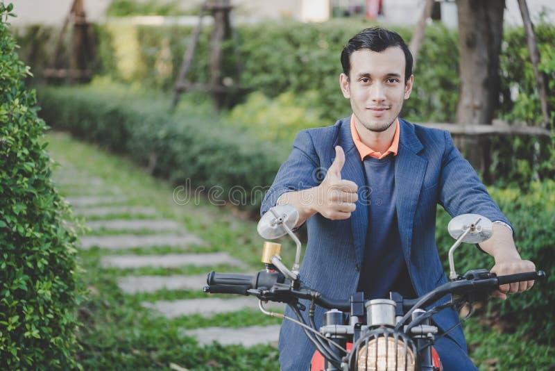 Homem de negócio que monta um velomotor no parque fotos de stock royalty free