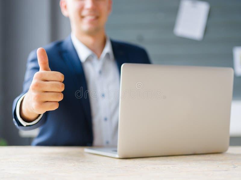 Homem de negócio que mostra um polegar até um portátil no fundo do escritório Conceito da tecnologia de Digitas fotografia de stock royalty free