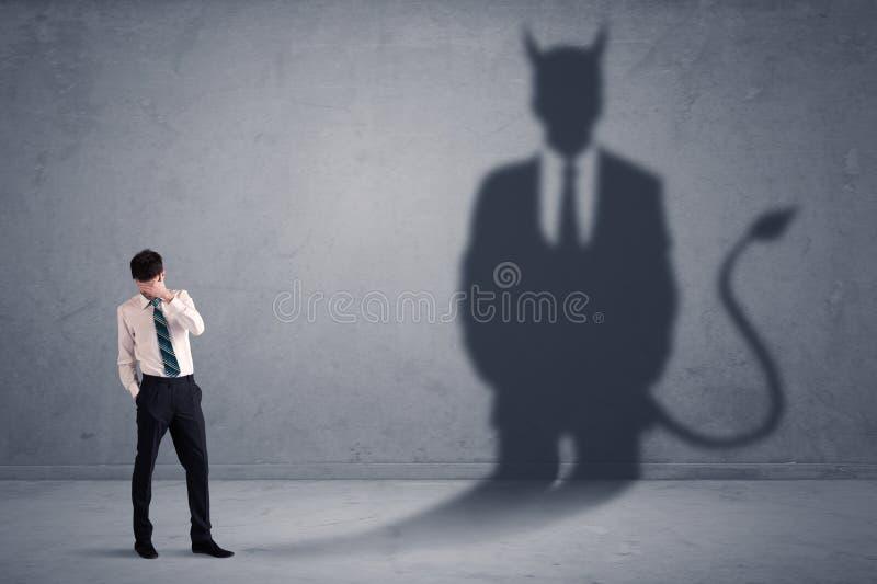 Homem de negócio que olha seu próprio conceito da sombra do demônio do diabo fotografia de stock
