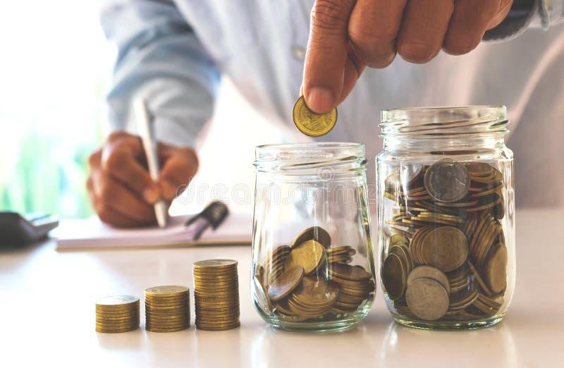 Homem de negócio que põe a moeda no banco de economia da garrafa de vidro e no accoun foto de stock royalty free
