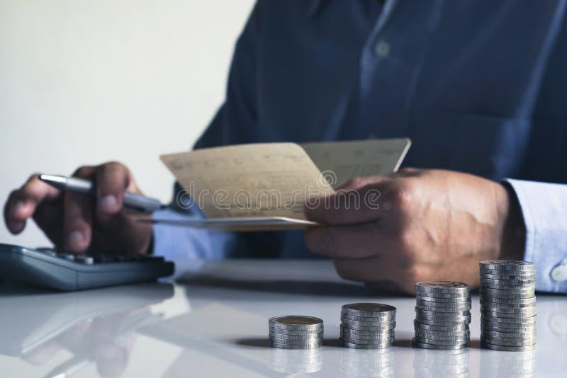 Homem de negócio que põe a moeda sobre a pilha do banco de economia do dinheiro e do accou fotos de stock royalty free