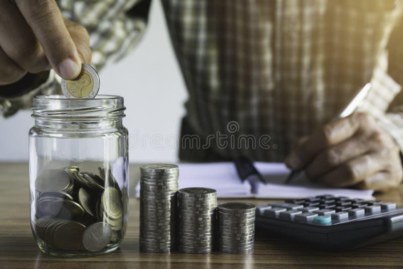 Homem de negócio que põe o dinheiro no frasco de vidro ao salvamento, conceito financeiro, explicando fotos de stock