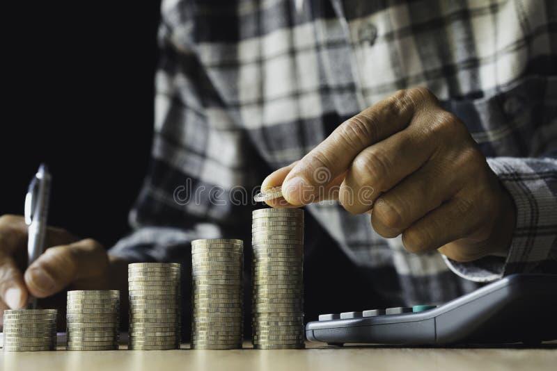 Homem de negócio que põe uma moeda sobre o banco de economia da pilha das moedas e para esclarecer seu dinheiro todo no conceito  imagem de stock