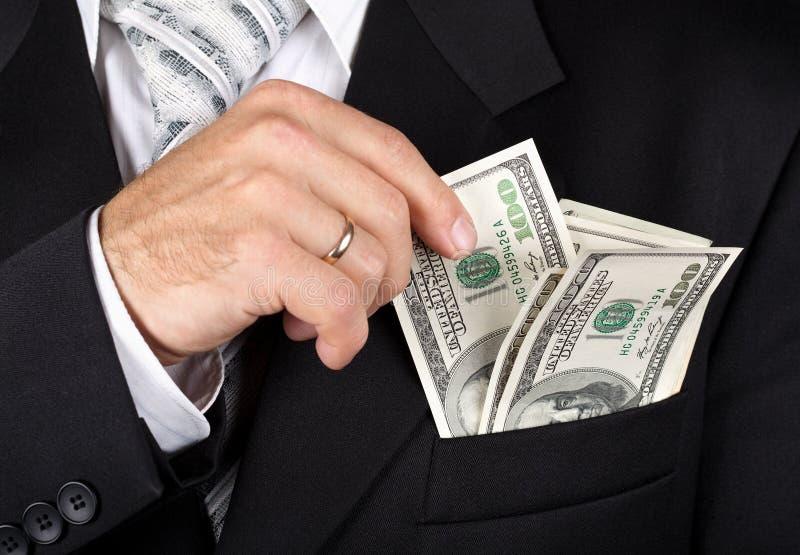 Homem de negócio que põr dollas em seu bolso imagens de stock royalty free