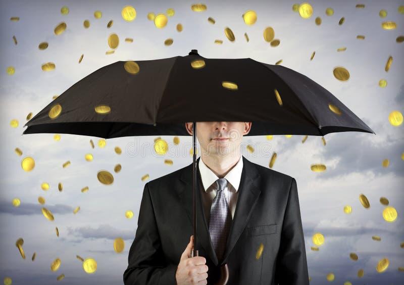 Homem de negócio que prende um guarda-chuva, queda do dinheiro fotografia de stock royalty free