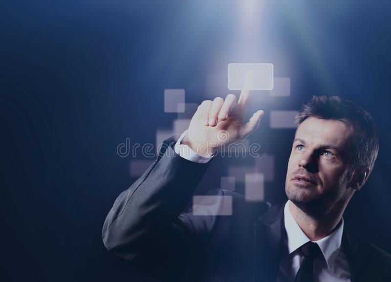 Homem de negócio que pressiona o botão virtual no fundo preto fotografia de stock