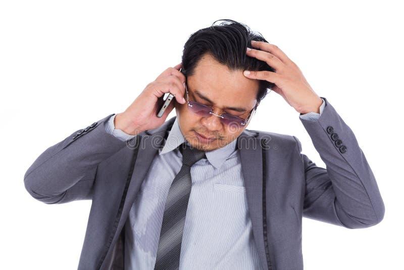 Homem de negócio que recebe más notícias no telefone celular isolado no wh fotos de stock royalty free