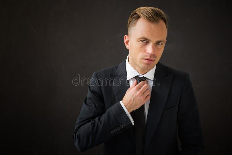 Homem de negócio que repara seu laço fotos de stock