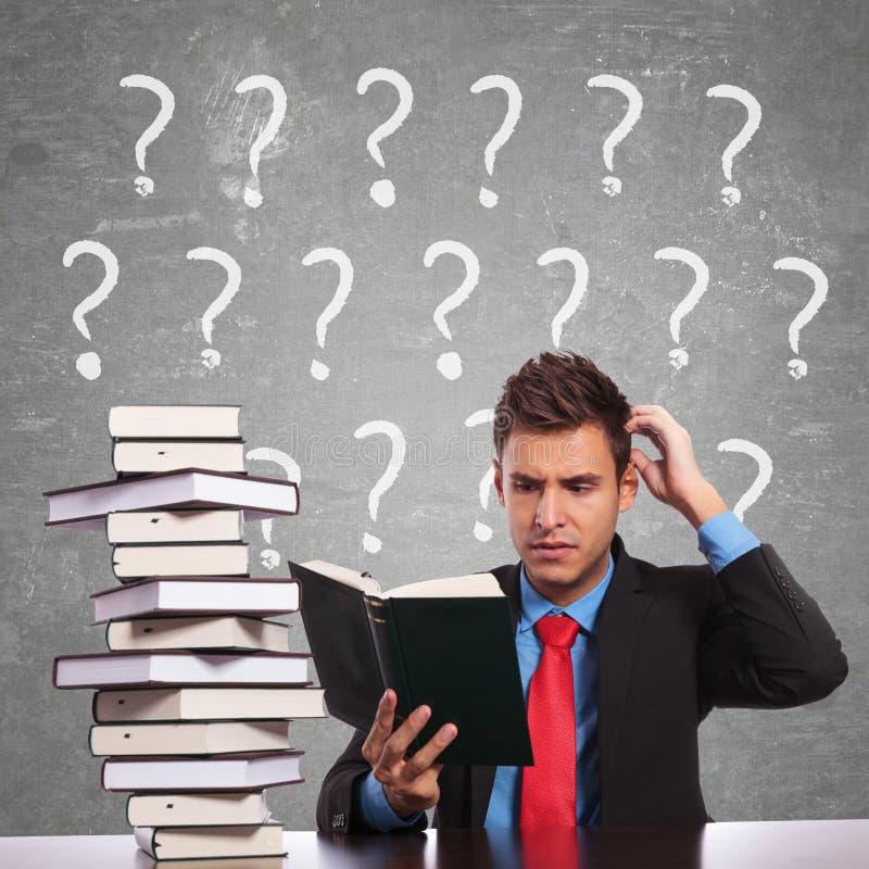 Homem de negócio que risca sua cabeça ao ler imagens de stock
