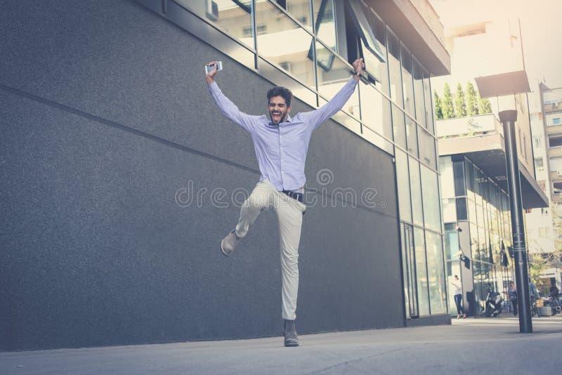 Homem de negócio que salta altamente Homem na rua da cidade fotografia de stock