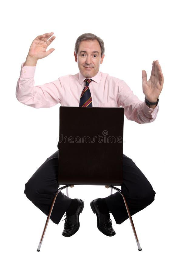 Homem de negócio que senta-se em uma cadeira foto de stock royalty free