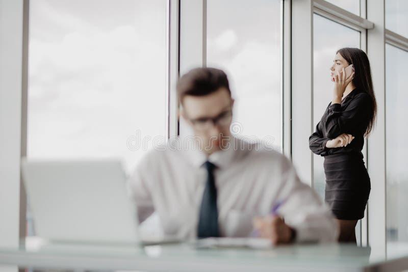 Homem de negócio que senta-se na mesa no escritório usando o portátil, quando mulheres que falam o telefone no fundo fotografia de stock royalty free