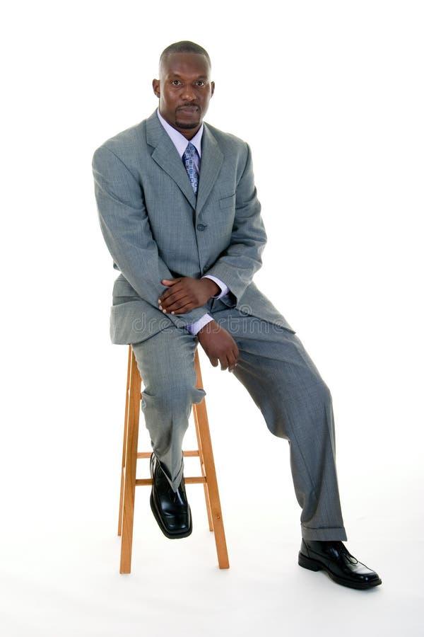 Homem de negócio que senta-se no tamborete imagem de stock