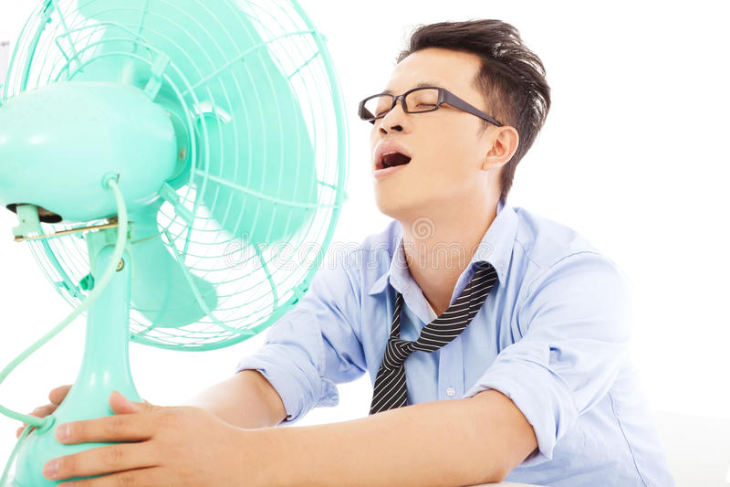 Homem de negócio que sofre um calor quente do verão com fãs foto de stock