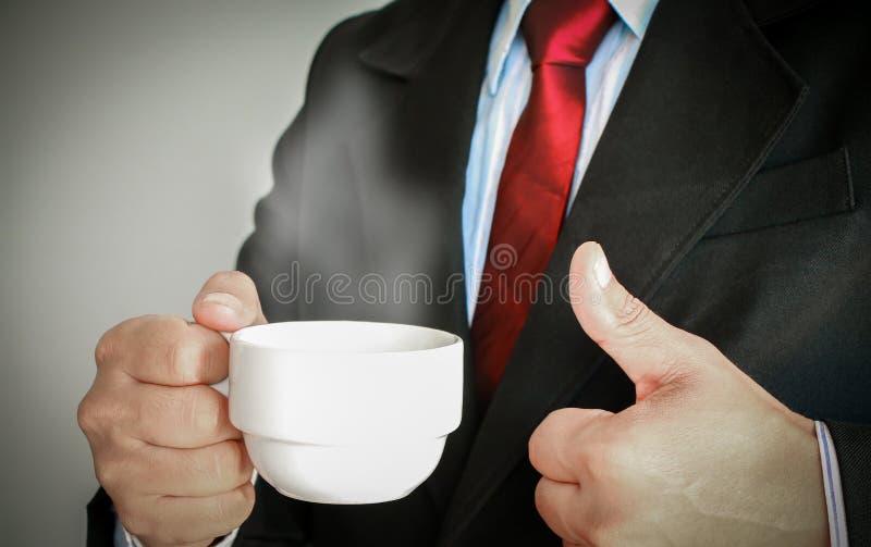 Homem de negócio que sorri com o laço vermelho que bebe uma xícara de café foto de stock
