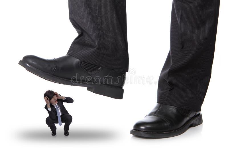 Homem de negócio que steping em um homem do medo fotos de stock