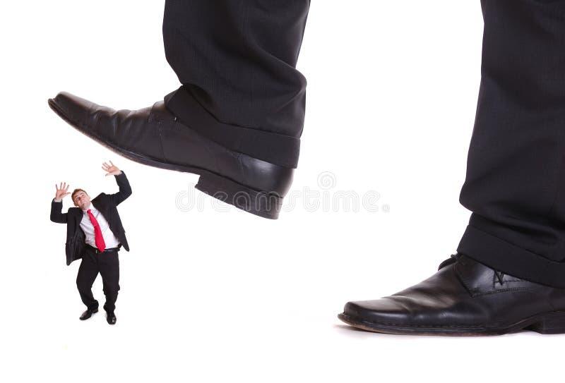 Homem de negócio que steping em um homem do medo imagem de stock royalty free