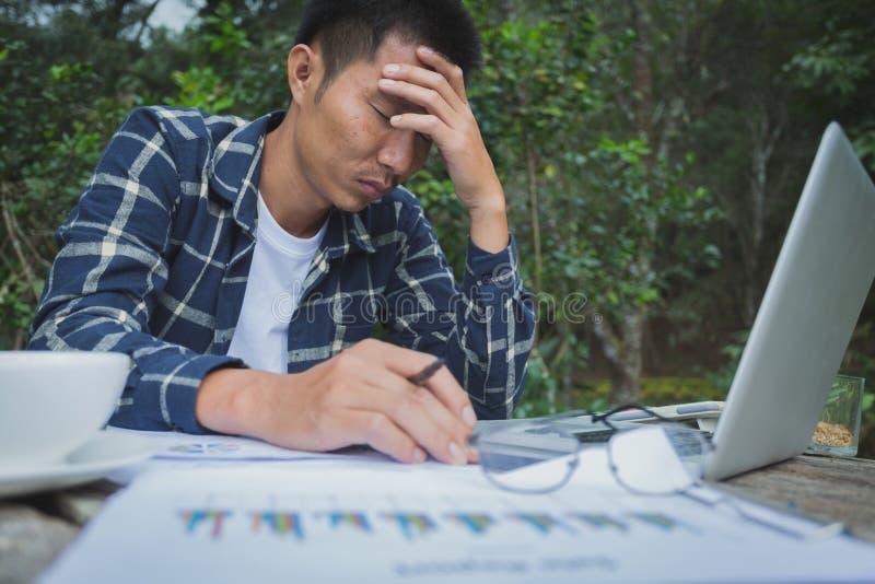 Homem de negócio que tem a dor de cabeça ao trabalhar usando o laptop imagens de stock royalty free