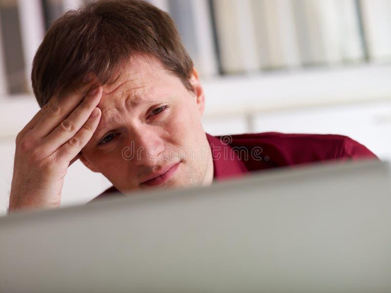 Homem de negócio que tem a dor de cabeça no escritório fotografia de stock royalty free