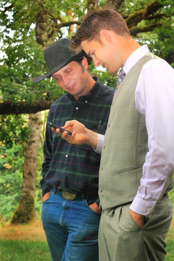 Homem de negócio que Texting com vaqueiro fotografia de stock