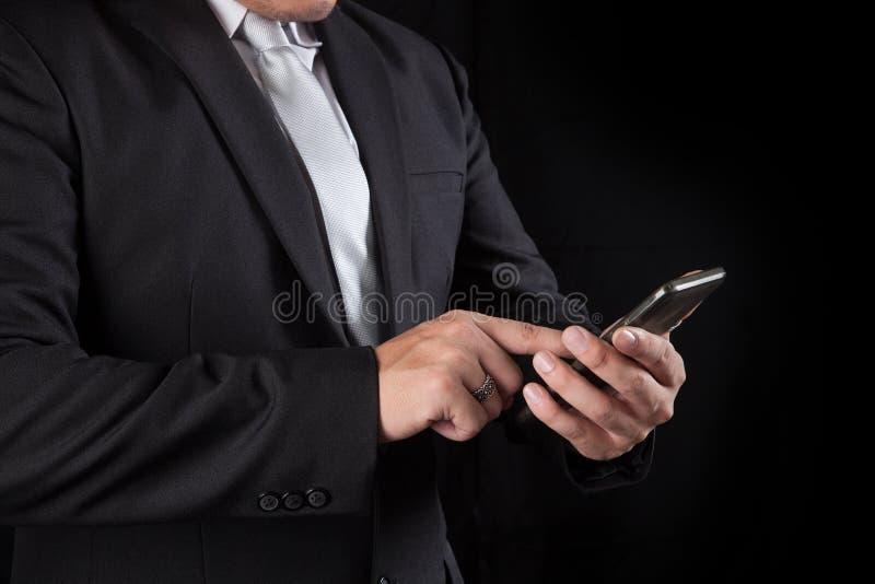 Homem de negócio que toca no uso da tela do telefone celular para conectar fotos de stock royalty free