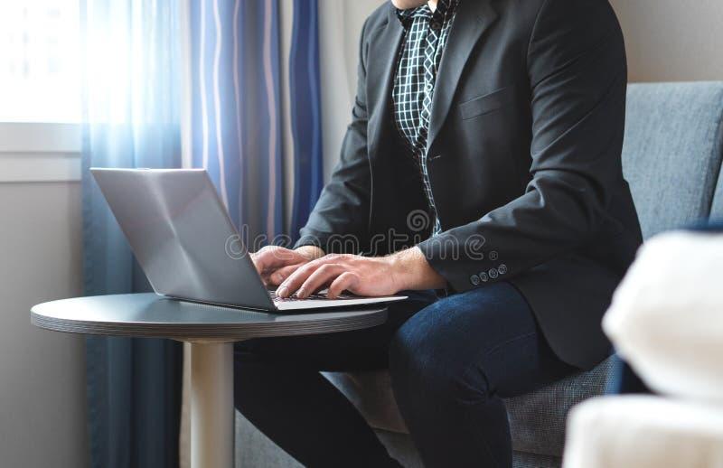 Homem de negócio que trabalha com o portátil na sala de hotel fotos de stock