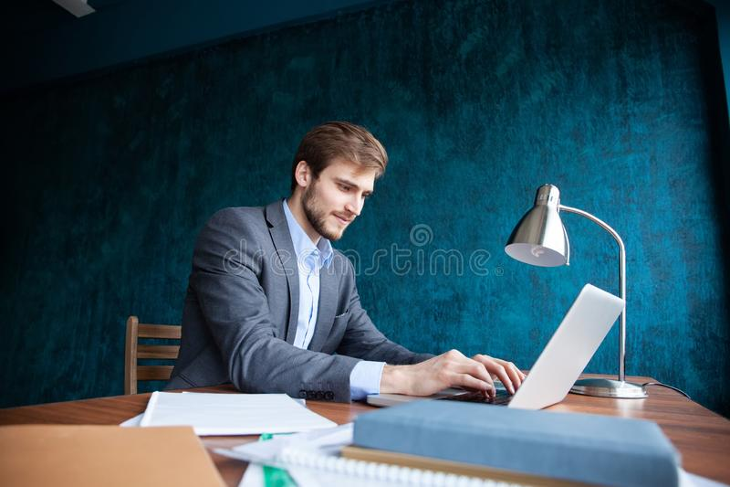 Homem de negócio que trabalha no escritório com portátil e originais em sua mesa, conceito do advogado do consultante imagem de stock royalty free