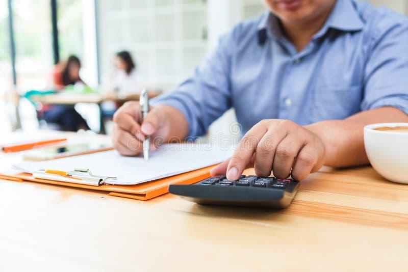 Homem de negócio que usa a calculadora ao cálculo imagens de stock