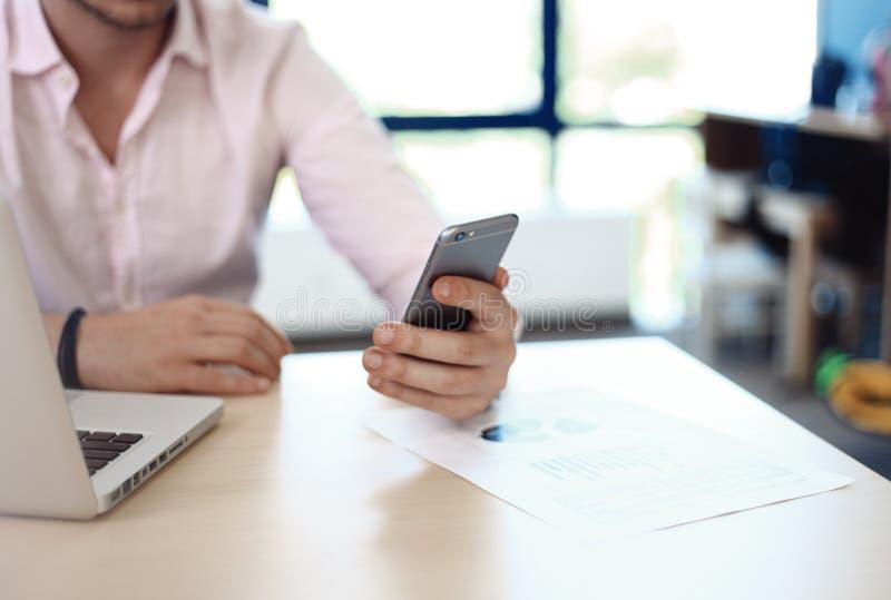 Homem de negócio que usa o Internet no smartphone e no portátil foto de stock